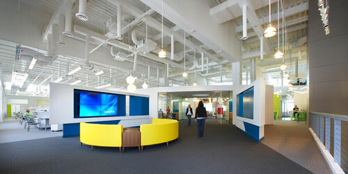 CompTIA headquarters lobby area showing white exposed ductwork, yellow couch and large digital display screen
